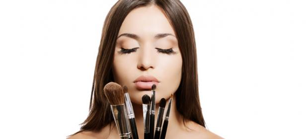 Young woman with makeup brushes